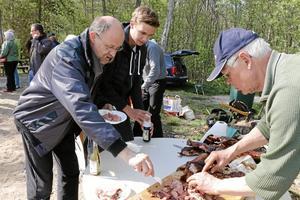 Nygrillat. Roland Gustavsson serverar potatissallad och vildsvinskött till Oskar Bäckgren och Leif Pettersson.