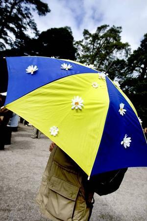 i stället för flagga. Ett paraply helt i dagens anda – gult och blått och med vita prästkragar på.