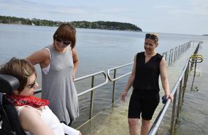 Malou Gustafsson testar handikapprampen i Bergafjärden med sina personliga assistenter Zandra Risberg och Ele Heinsaar.