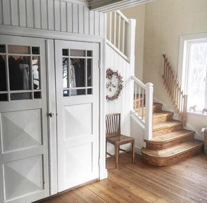 Återbrukade gamla ytterdörrar och varma furugolv i hallen på Högbackagården.