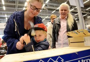 Slående insats. Tävlingen i byggföretagets monter går ut på att slå i en spik med så få slag som möjligt. Jesper Eriksson och Emelie Carlsson hjälps åt. Intill står Sara Nilsson.