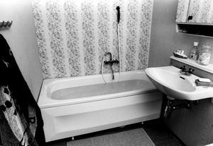 Så badade vi 1977. Blommig tapet på fondväggen, badkar och handfat med kranar för kallt och varmt vatten.