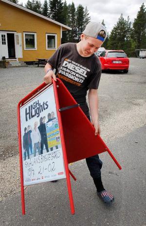 Jesper Halvarsson bär fram dansaffischen till vägen.