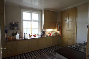 Köket på bottenvåningen har björkådringsmålade luckor och snabelhandtag.