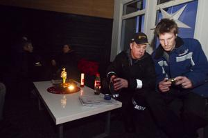 Medarbetarna och bröderna Jonas och Tomas Klang kollar in senaste information i mobilen. Jessica Strömstedt, receptionschef och husfrun Thory Hansson, begrundar situationen i bakgrunden.