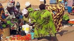 Grönsakshandel: Kvinnorna ofta klädda i vackra färggranna kläder till vardags som här vid grönsakshandeln.