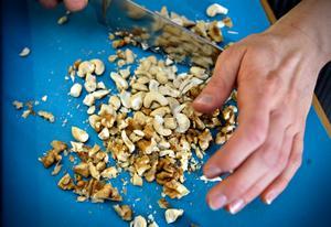 Cashewnötter och pekannötter hackas fint. Det märks snabbt att Elin har gjort det här förr.