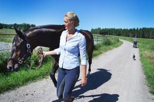 Evelina Johannisson leder hästen Caprino från en hage till en annan. Sambo, dotter och hund kommer efter.