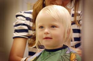 Elle Andersson ser sig själv i spegeln medan frisören Sandra Frejding klipper henne.