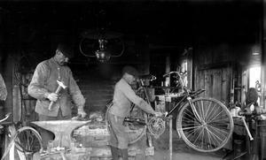 Far och son i smedjan. Bilden troligen från 1910–1915. Pappa Lars vid städen och sonen Valdemar tar hand om cykeln.  Foto:Sockenbilder, Högs hembygdsförening.