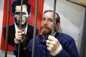 Konstnär och filosof bakom galler. Gustav Kape Lindqvist, som öppnar sin nya utställning i dag gör helst inte porträtt. Men bilden intill honom är ett undantag som bekräftar regeln och starkt påminner om en bekant österrisk filosof. Foto: Tomas Larsson