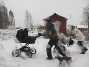 Mammor, barn och hundar kämpar sig fram i snöblasten i slutet av oktober.