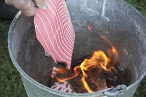 En servett som har impregnerats kastats ner i hinken tillsammans med en annan brinnande servett.