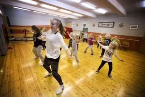 Danslärarna Louise Forsström och Felicia Eneljung står framme vid spegeln och går igenom koreografin till låten #thatpower med Will.i.am och Justin Bieber som de påbörjade veckan innan. Sedan dansar gruppen igenom det de lärt sig hittills.