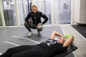 Tränaren Elin Ivarsson håller koll medan Erica Berglund gör situps.