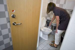 En städare gör rent toaletten på en arbetsplats.