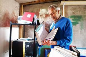 Axel Skoger, ordförande i Hjärt- och lungsjukas förening går igenom vattenskadade pärmar som räddats från det brandskadade huset.