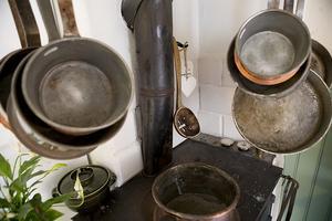 Den gamla pittoreska vedspisen med slevar och pannor har en given plats i köket.