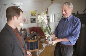 Håkan Klang gratuleras till vinsten i novelltävlingen med blomster.