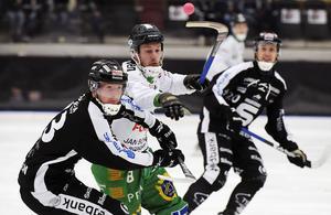 Hammarbys Per Einarsson uppvaktas av Sandvikens Ted Haraldsson och Daniel Bäck.