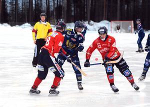 Patrik Allansson-Roos i kamp med två Unik-spelare.