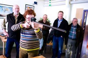 Kommunalrådet Lena Olsson (BE) testar den nya skyttesimulatorn. Sven-Gunnar Sivertsson, ordförande för Bergs jaktvårdskrets, instruerar.