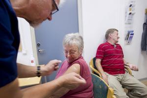 """FÅR PLÅSTER. Ett plåster på såret får Birgitta Wallberg efter sprutan och uppmaningen att för säkerhets skull stanna kvar i väntrummet i 20 minuter ifall att hon skulle få en allergisk reaktion. """"Det kan hända även om man aldrig fått det förr"""" förklarar distriktssköterskan Ulf Strömbergsson. I bakgrunden väntar maken Åke Wallberg på sin tur."""