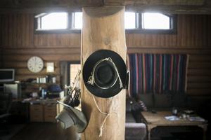 De obligatoriska cowboyhattarna hänger på en av timmerstockarna.