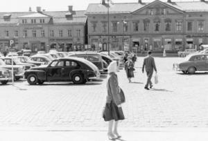 Liv och rörelse på Stora torget 1959. Då var parkering tillåtet på torget. Bilar stod i rad efter rad.