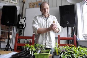 Anders Persson med vårens odlingar – och en nykläckt kyckling. Allting ingår i kretsloppet på hans gård.