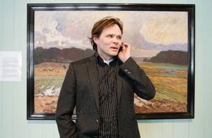 Hans farfars far Anton Genberg målade tavlan som Mikael Genberg står framför. Själv är han mer framgångsrik som talare, idékläckare och hotellbyggare än som målare.  Foto: Ulrika Andersson