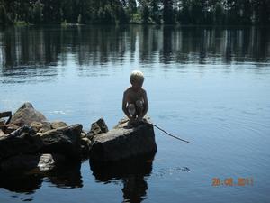 En bild på min son som sitter och väntar ut gammelgäddan en solig dag på besök hos våra släktingar i Änga/Bollnäs.
