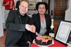 Kommunalrådet Abbe Ronsten (S) och Lotta Bergstrand (FP), ordförande i näringslivs- och utvecklingsutskottet, firade kommunsloganens framgångar med tårta.