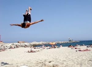 Free fallingKillar som hoppar högt på stranden.