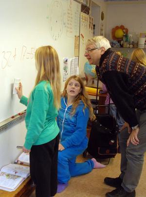 Linnea Larsen och Jasmine Ericsson får hjälp av rektor Göran Garmo med att räkna ut ett klurigt mattetal på svarta tavlan - som numer är vit.