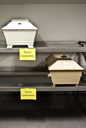 I det sterila kylrummet väntar två kistor på att bli kremerade.