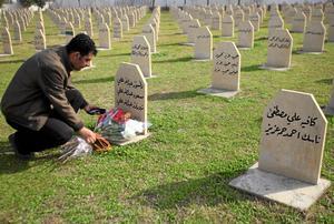 Glömmer aldrig. En man lägger blommor på graven för ett av offren för gasattacken i Halabja 1988.Arkivbild: Yahya Ahme/Scanpix