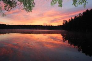 Bilden är tagen vid sommarstugan 03:30 en tidigt morgon, i sjön speglar sig himlen i fantastiska färger och molnen dansar över sjön.