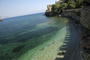 Turkiska grabbar svalkar av sig i det klara havet bortom gületbåthamnen i Alanya.