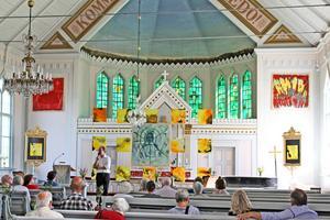 Curator Gert Andersson talar om kreativiteten som en andlig kraft.   Konstverket i mitten framför altaret är Tobi Andersson-Fägerskiölds