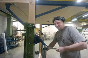 Clas Häggblom monterar beslagen på en vipport. Han har jobbat på Edsbyporten i tio år.