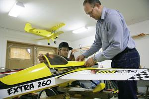 Micke Andersson, till vänster, och Fredrik Lenz vid ett av modellflygplanen i flygklubbens modellflygverkstad.