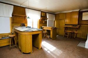 Interiör från brukskontoret där de gamla räkenskapsböckerna fortfarande ligger uppslagna på skrivpulpeterna. Byggnaden är numera privatägd, men