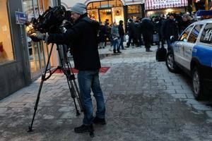 Tv-team och människor som passerar platsen på Bryggaregatan / Drottninggatan i centrala Stockholm där en man sprängde sig själv till döds på lördagseftermiddagen.