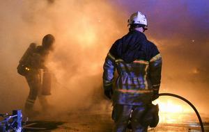 Räddningstjänsten släcker en brinnande bil i Malmö.