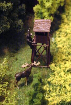 Ett jakttorn med en älg vid sidan och en björn som håller på att klättra uppför tornet för att läsa lusen av jägaren finns i ett skogsparti.