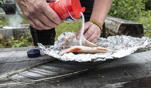 Ingela kryddar med salt och citronpeppar och paketerar in fisken i folie. Paketet placeras direkt på glöden.