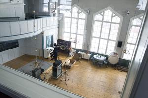 I kontrollrummet på övervåningen har de satt in en stor fönsterruta för att kunna blicka ut över den stora kyrksalen.
