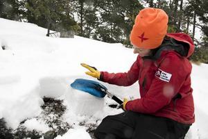 Karin har frilagt en pelare med snö. Nu bankar hon på den för att simulera en skidåkare och se om snön släpper. Först slår hon tio gånger med handflatan, sedan tio gånger genom att svinga underarmen, och sist tio gånger med hela armens tyngd. Ju lättare snölagren delar på sig, desto större risk för lavin.