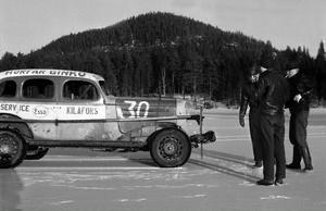 En Stock Car-bil inspekteras av nyfikna i samband med en tävling på 1950-talet.